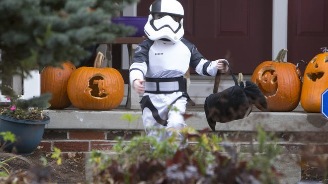 FILE - Oliver Traylor dresses as a storm trooper scores candy during trick-or-treating in Jackson Township, New Jersey, on Sunday, Oct. 29, 2017.