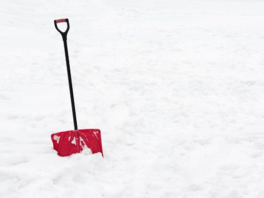 Red snow shovel standing in snow.