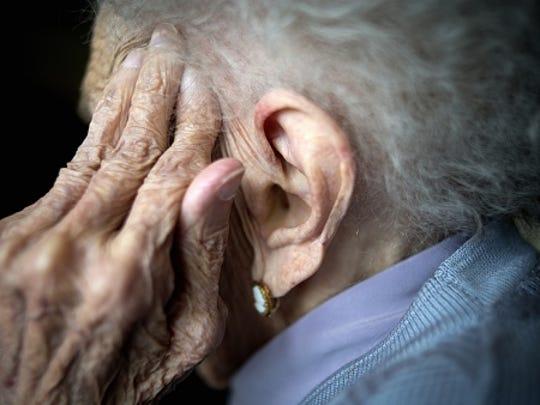 Portrait of a centennial woman in nursing home, hand