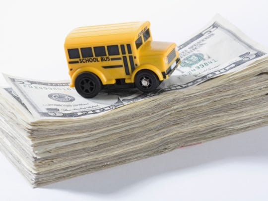 Close-up of a toy school bus on a stack of US dollar bills