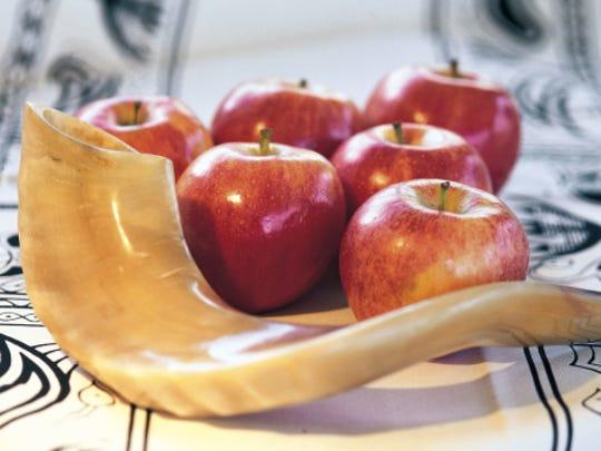 A shofar horn for Rosh Hashanah sits near apples. Judaism's