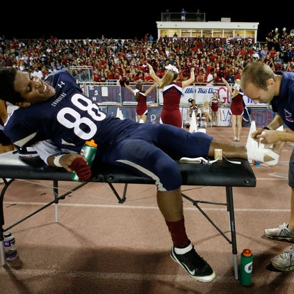 Athletic trainer Trevor Muth of Tempe McClintock High School tapes Travis Thomas' ankle during a football game last week against Tempe High. Hawaii is the only state to have a trainer in every high school, with funding earmarked for the positions.