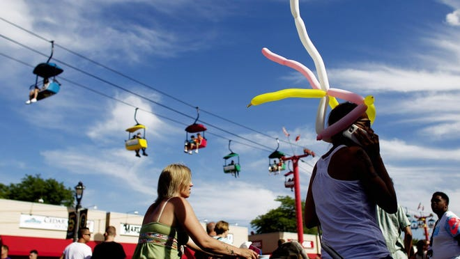 A woman wearing a balloon headpiece walks along the Summerfest grounds.