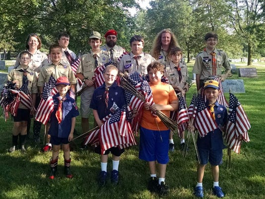 Scouts from Webster Troops 108 and 110 and Pack 108 worked together to collect flags from Holy Trinity Cemetery. (Provided photo)