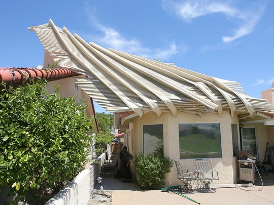 A metal patio was bent up and over causing it to touch a neighboring house at the Palm Desert Country Club after Thursday's storm damaged the area.