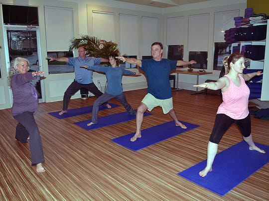 Yoga instructor Debi Lewis demonstrates proper Warren II postion to, from left, Kirk Lomax, Rachel May, Fitness Pluss owner Marty McCubbins and Suzanah Round. The yoga pose is great for building strength, stamina, balance and focus.