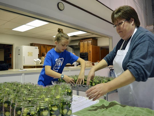 """Donna Mabus, right, Ventures instructor at Brandon Elementary and Katelyn Griner, 10, work together filling a cart with jars of cucumbers as they prepare for the next step in making dill pickles as part of their """"I'm in a Pickle"""" Pickle project."""