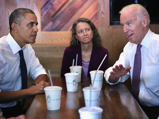 President Barack Obama (left) and Vice President Joseph Biden (right) meet with local workers, including Meredith Upchurch, at the Shake Shack restaurant in Washington, Friday, May 16, 2014.