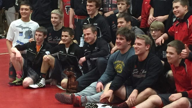 St. Johns wrestlers pose for a photo after beating DeWitt to capture a Division 2 district title.