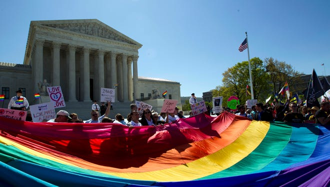In this April 28, 2015, file photo, demonstrators stand in front of a rainbow flag of the Supreme Court in Washington.