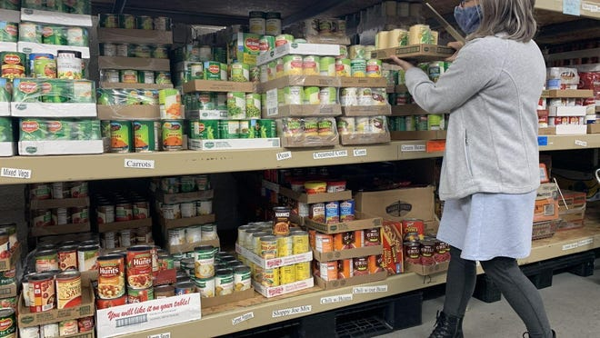 A volunteer stocks the food pantry at Love in Action in Grand Haven.