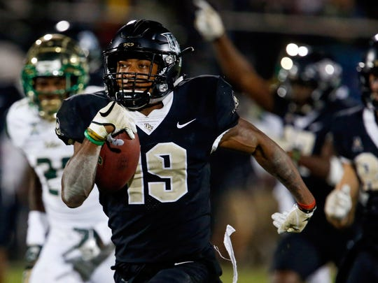 UCF Knights kick returner Mike Hughes (19) runs back the kick 94 yards for the go ahead scorer against the South Florida Bulls during the second half at Spectrum Stadium.