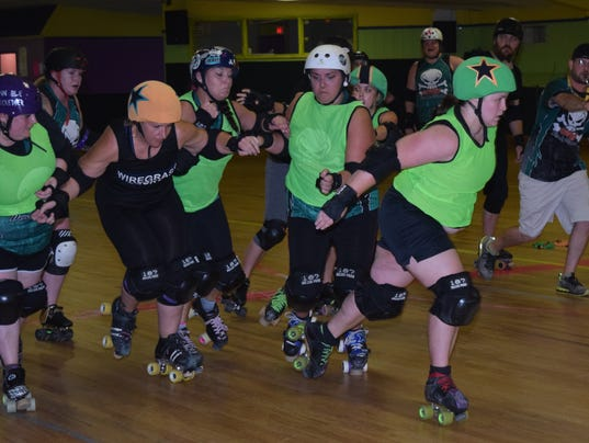 """Devon """"Running Scared"""" Wigle (front, green helmet) and Mindy """"M. Kickin' Some"""" Bozine (back, yellow helmet) are the jammers in a practice name at a recent Cenla Derby Dames practice at Skateville on Highway 28 East in Pineville. Timberly """"Silence of the J"""