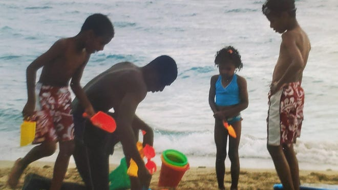 John Francis builds sandcastles with his children.