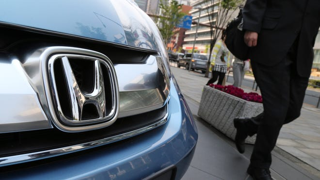 In this April 25, 2014 file photo, a man walks past a Honda model on display at Honda Motor Co. headquarters in Tokyo.