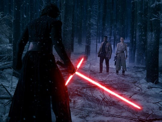 Kylo Ren has his lightsaber ready against Finn and Rey in 'The Force Awakens.'