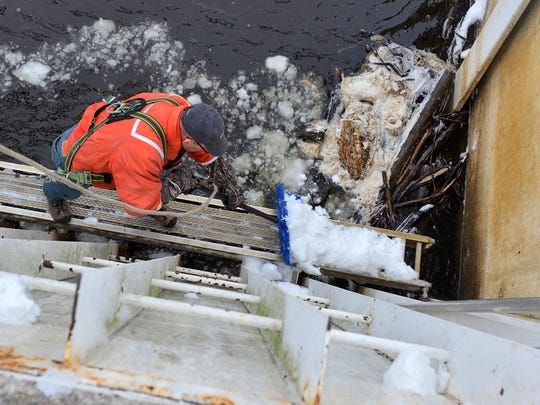 St. Cloud Hydroelectric Dam Plant Supervisor Daryl Stang clears snow from a catwalk along the trash racks leading into generating unit one Wednesday, Dec. 2 before cleaning the racks. Debris flowing down river collects in the racks and needs to be removed to keep water flowing smoothly into the generators.
