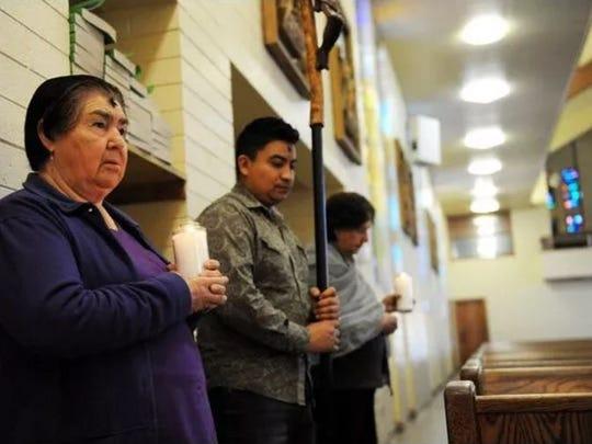 Las personas que asisten en dar la bendición se preparan para los servicios en la iglesia Santa Maria.