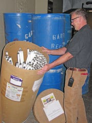 Facilities employee, James Beard, shows spent fluorescent tubes that will be shipped off for recycling.