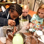Jadyn Cunningham, 12, left; Caroline Boudreaux, 11, middle; and Kaitlin Lowry, 13; stir the melting chocolate into the bowl as they make lava cake during Kids Cooking Camp at the Kitchen Table on Wednesday. The week-long camp teaches children how to cook dinners and desserts.