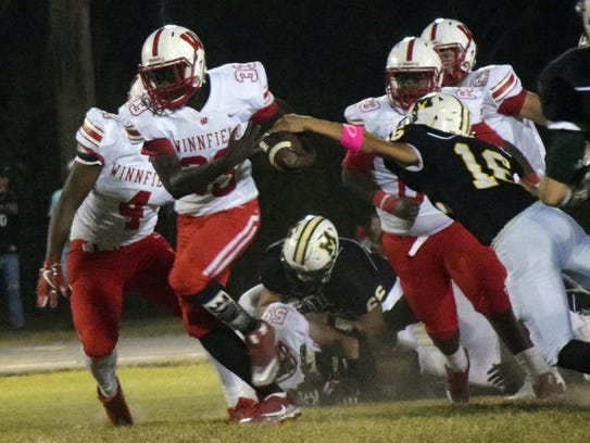 Holy Savior Menard High School's Colby Lovely (16, right) gets a hand on Winnfield Senior High School's Isaiah Loucious (33, left) Friday, Oct. 20, 2017.