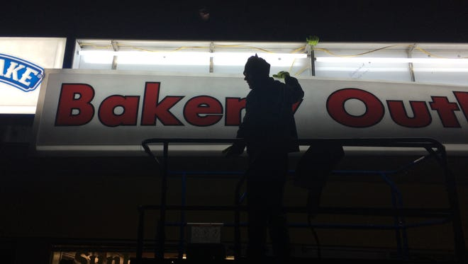Workers from American Made Signs install a new sign at the Flowers Baking on West Main Street in Waynesboro, Virginia. Feb. 10. 2015