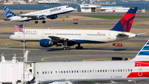 JetBlue, Delta and American airlines planes are seen at Boston's Logan International Airport on April 13, 2015.