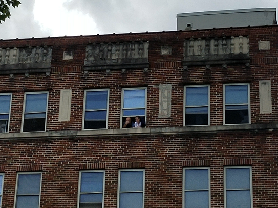 Two people look from the top window of 15 Woodfin St.
