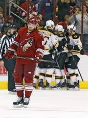 Arizona Coyotes' Mikkel Boedker skates away dejectedly as the Boston Bruin celebrate a goal scored by teammate Brad Marchand in Glendale.