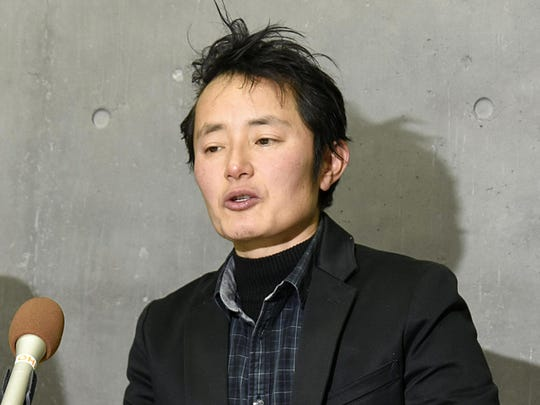 In this Jan. 24, 2019, photo, Takakito Usui, a transgender man, cries while speaking during a press conference after Japan's Supreme Court handed down in Okayama, western Japan. Japan's top court has upheld a law requiring sterilization for transgender people to get their gender changed on official documents but acknowledged the law is increasingly becoming out of step with the international standard.