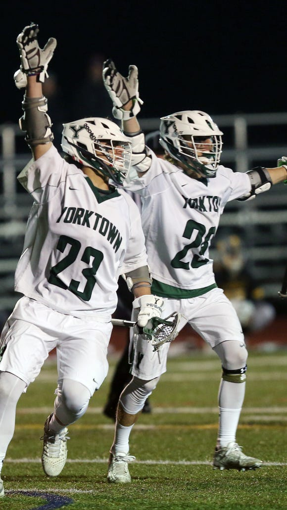 From left, Yorktown's Hunter Embury (23) and Shane Dahlke (29) celebrate a goal by Embury against Saint Anthony's during boys lacrosse action at Yorktown High School March 27, 2018. Yorktown won the game 10-5.