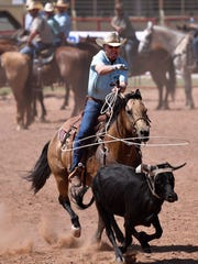 Ricky Snowden throws his rope over the head of a calf during the Gideon Carmichael Memorial Team Roping on Friday in Haskell. The Wild Horse Prairie Days renamed the contest this year after a local helicopter pilot who died last year and was an avid team roper.