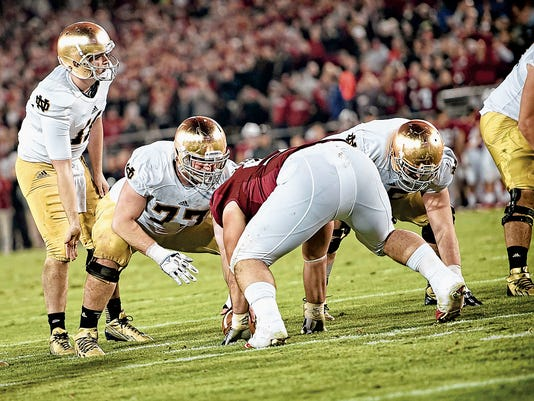 Notre Dame center Matthew Hegarty (77) prepares to snap the ball to quarterback Tommy Rees (11) during a game against Stanford on Nov. 30 at Stanford Stadium in Stanford, Calif.