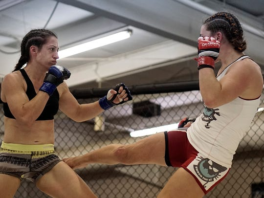 Allison Ainley, left, and Gemma Sheehan tries to land a kick in her amateur fight with Allison Ainley in Saturday night's Big Guns 17 MMA show in Fairhaven Hall. Sheehan won by unanimous decision.