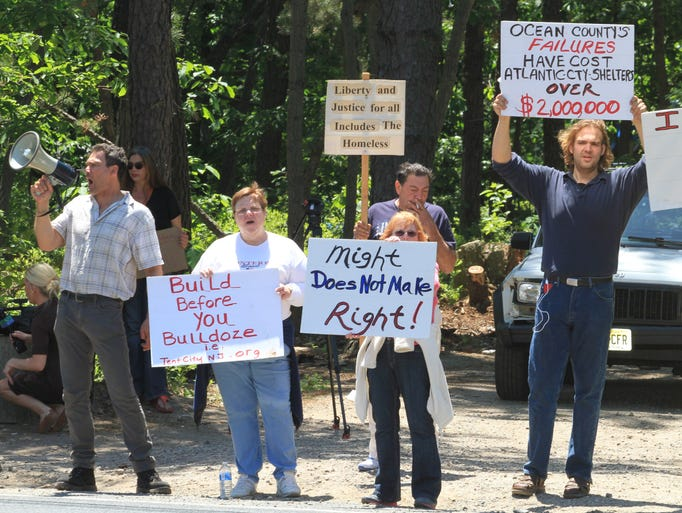 ASB 0603 Lakewood Tent City  Tent City coordinator, Minister Steve Brigham, left, is joined by Tent City residents and volunteers as they protest outside the encampment, Monday, June 2, 2014. Lakewood, NJ - Photo by Mary Frank