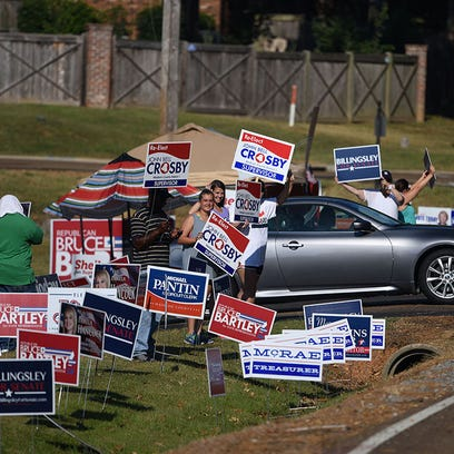 Campaign supporters stand in a sea of signs outside