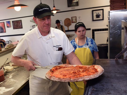Trainee Emma Crow, background right, watches as co-owner Walter Gloshinski removes a classic New York-style pie from the oven at Smiling with Hope Pizza. Gloshinski and his wife Judy are re-opening the pizzeria on Sept. 3, 2019, after it had been closed since June so Walter Gloshinski could have a double hip replacement.
