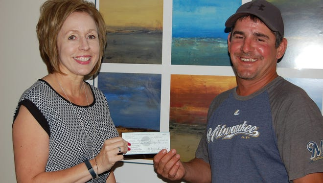 Mike Melzer, of Allenton, at right, is the grand prize winner of this year's Agnesian HealthCare Foundation Charity Open Raffle first place prize - a 2015 Ford Escape or $15,000 cash prize. Melzer is shown accepting the cash prize with Michelle Ries, Foundation events coordinator.