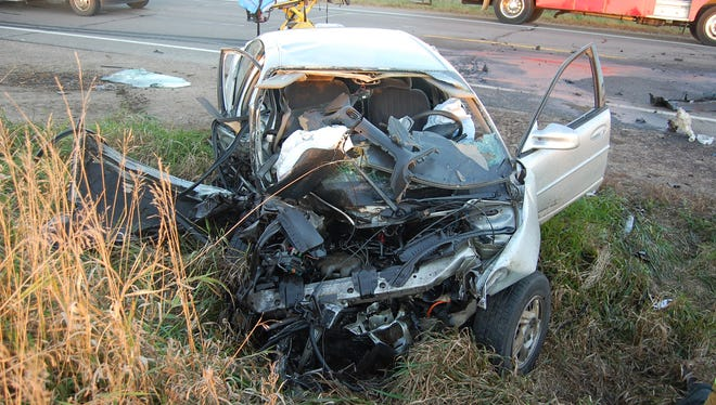 A car involved in a head-on crash Saturday sits by the side of State 73 in Clark County. Two people in the vehicle suffered incapacitating injuries, according to police.