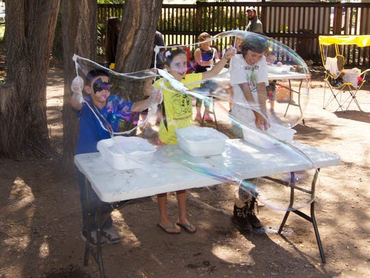 Youngsters try their hands at making bubbles at the