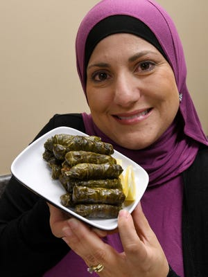 Ghada Ayesh holds a plate of stuffed grape leaves as an  example of the international food types which will be offered Saturday at the International Food Festival at the Worlds Fair Park.