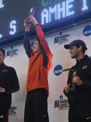 Ventura High graduate Brandon Lum holds up the Division III championship plaque after his record-setting swim in the 200-yard butterfly. Lum is a sophomore at Washington University in St. Louis.