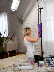Singer and songwriter Lindsay Ell paints a guitar that
