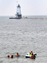 With the Ludington Light in the background, swimmers and sunbathers at enjoy at day at the beach on Lake Michigan at Ludington on Thursday, July 5, 2018.