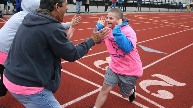Robert Sanchez, from West Irondequoit's Dake Junior High School, gets a pair of high-fives from Sonny Mortillaro, a student at Dake, as he finishes the 100-meter dash.