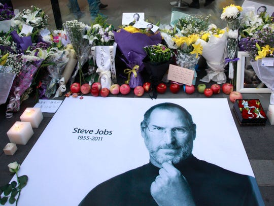Fresh apples, flowers and a large poster of Steve Jobs