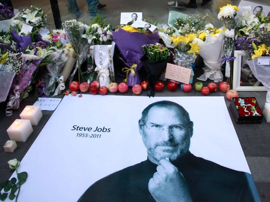 Fresh apples, flowers and a large poster of Steve Jobs are placed outside an Apple retail store in Beijing, China in 2011.