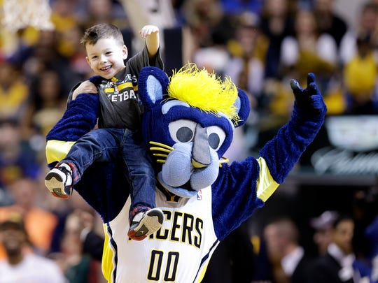 Indiana Pacers mascot Boomer holds a young child on his shoulder during a timeout in a game against the Orlando Magic at Bankers Life Fieldhouse on March 31, 2016.