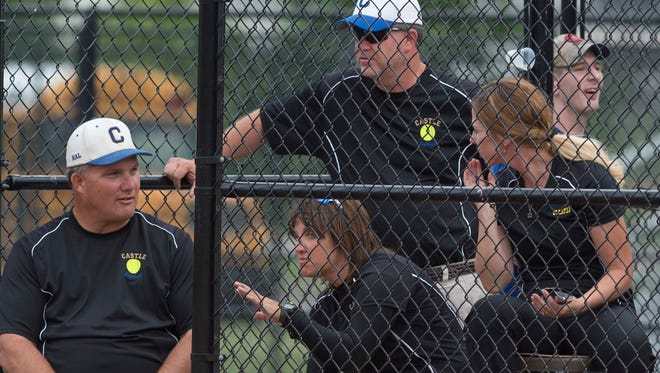 Castle softball coaches, clockwise from left, Pat Lockyear, Scott Fischer, Elanie Arnold and Becky Lis gather for some last-minute strategy in the dugout at North High School before their sectional game against Central Tuesday evening. Arnold and Lis were both players under Lockyear.