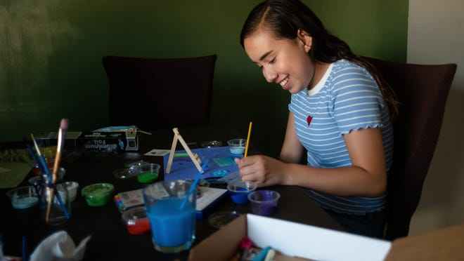 Regina Loayza, 17, of New Albany, applies paint to a project as part of Proyecto Mariposas on Friday at her family's home in New Albany. Proyecto Mariposas is a non-profit group that provides community and support for Latina girls and their mothers.